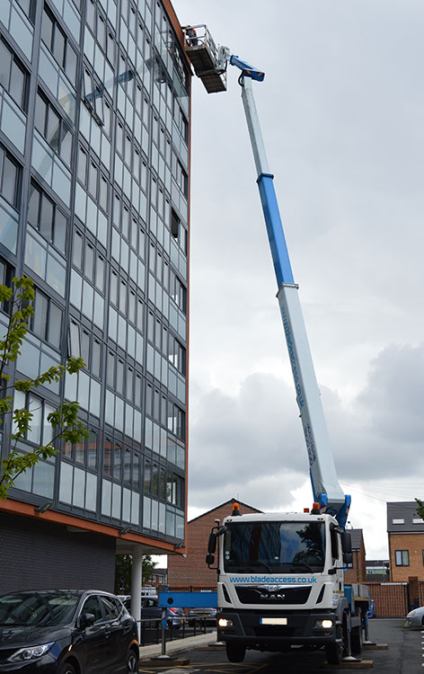 A 32m truck mounted platform being used for window cleaning on office buildings