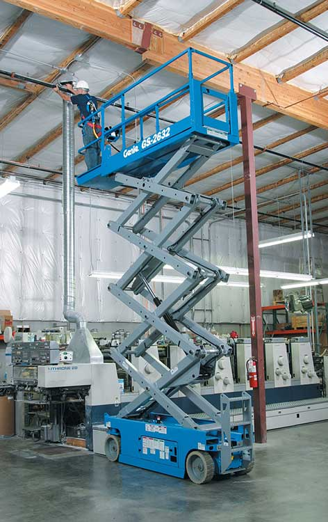 A technician uses a 10m Electric Scissor Lift Hire platform to gain access to repair a roof indoors