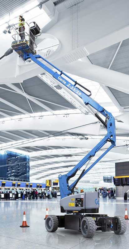 A cherry picker working indoors in an airport terminal