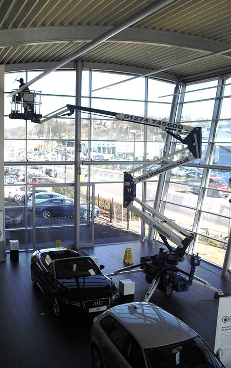 track mounted spiderlift platform hire machine used to gain access in a car showroom